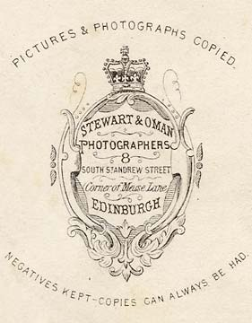Enlargement of the back of a carte de visite of a young man in a large suit by Stewart & Oman