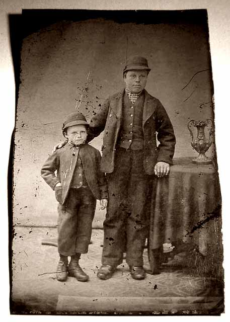 Unframed quarter-plate tintype photograph of a man, a boy and a trophy