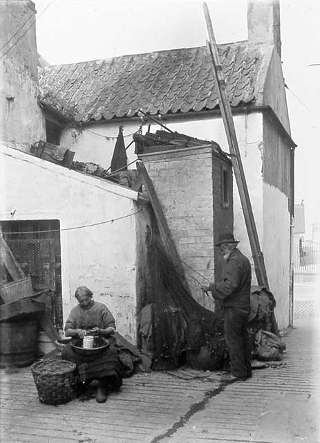 Newhaven Streets  -  Wester Close with a man mending nets and a woman shelling shell fish  -  1880s