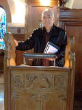 George Robertson standing at the lectern in Robin Chapel in 2009.  George carved this lectern 60 years earlier