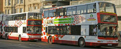 Two buses in Princes Street, showing  older and more recent examples of the Lothian Buses harlequin livery  -  November 2005