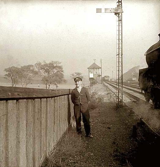 A railwayman stands beside the track as an engine passes heading towards a signalbox.  Where is it?