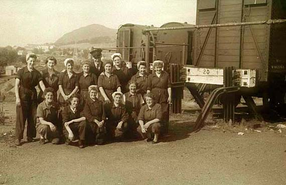A group of 14 cleaners at Craigentinny, with Arthur's Seat in the background