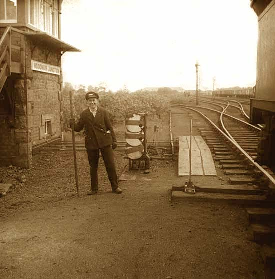 A railway worker stands beside the railway in front of Woodmuir Junction signal box in West Lothian