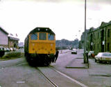 A train passes Granton Harbour and crosses West Harbour Road on its final approach to the Texaco sidings at Granton