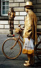 Golden Cycle Man stops to watch another entertainer in the Royal Mile