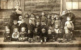 Dumbiedykes  - A group of 30 children and two men, all on the pavement  -  around 1922