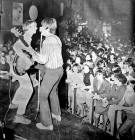 Two of the Moonrakers pop group performing on stage at McGoos in the 1960s