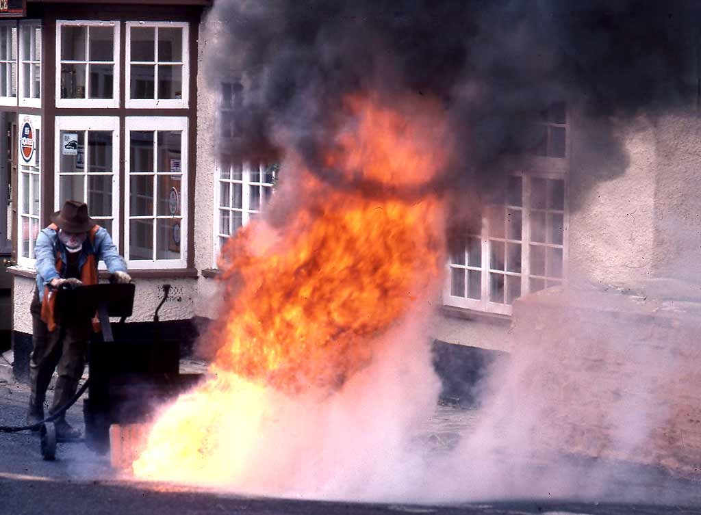 People at work around Britain  -  Burning tar off the road at Exford, Somerset, 1985