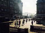View from the steps of Register House  -  Looking towards Edinburgh Castle with pedestrians at the East End of Princes Street in the foreground