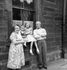 Forbes Wilson with his cousin, Lorraine, and his grandparents outside No 28 Thorntree Street, Leith  -  1960